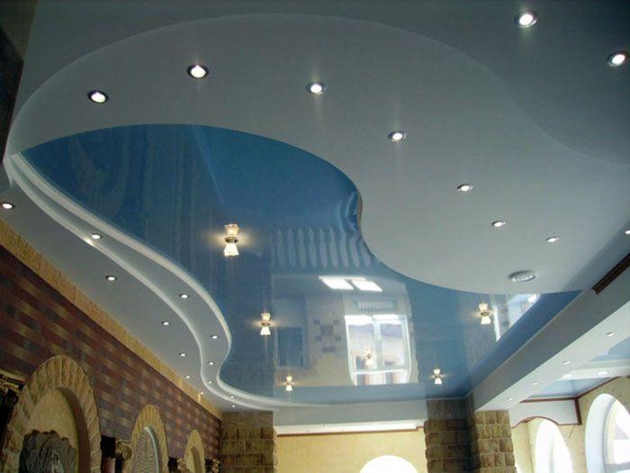 На снимката има лъскав опънат таван на две нива за залата: като повърхността на езеро